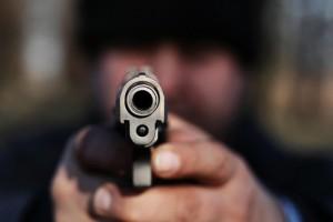 Man pointing gun directly at camera.