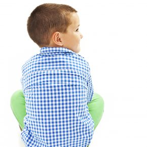Back view of little boy looking on side. Isolated on white background